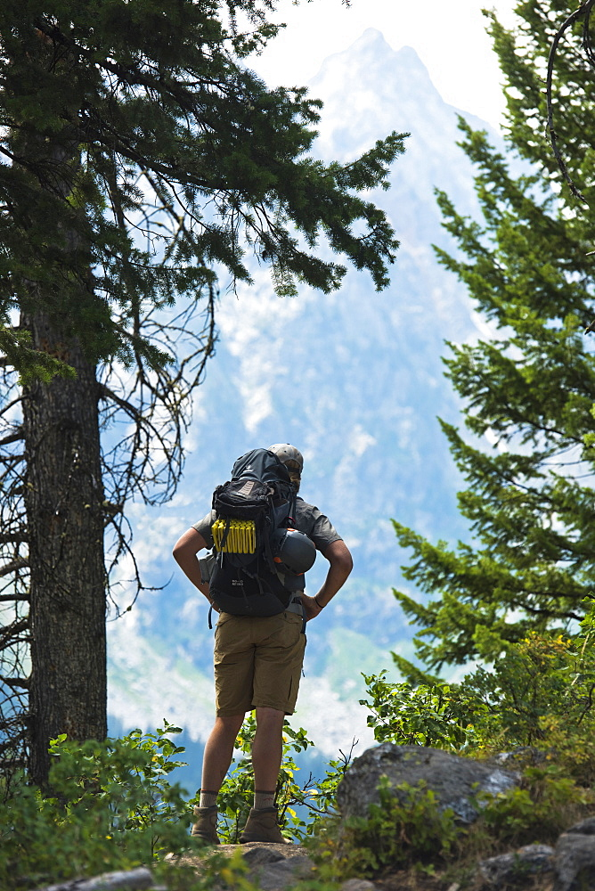 Rear View Of A Backpacker Looking At Teton Mountains In Jackson Hole, Wyoming