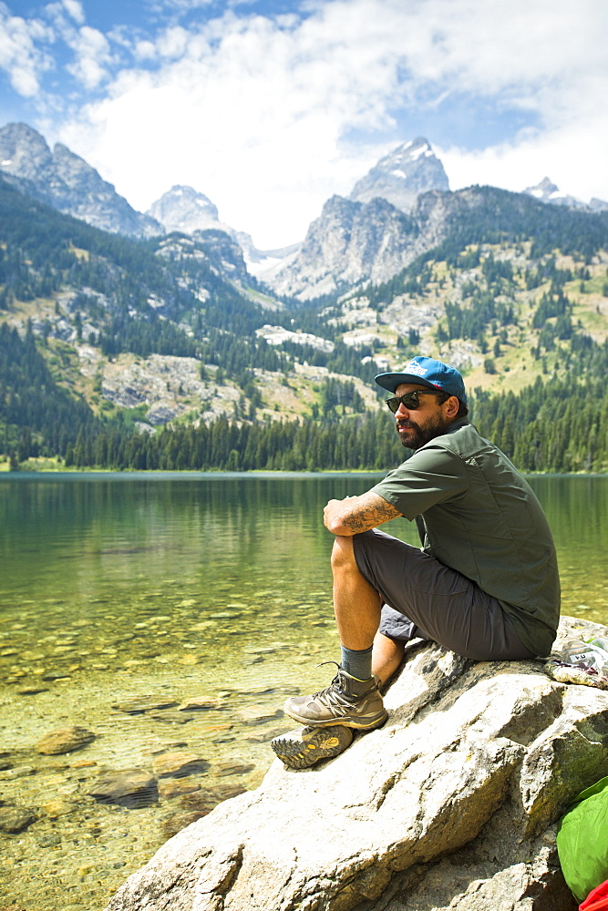 A Backpacker Sitting On Rock At A Lake Of The Grand Teton Mountains In Jackson Hole, Wyoming