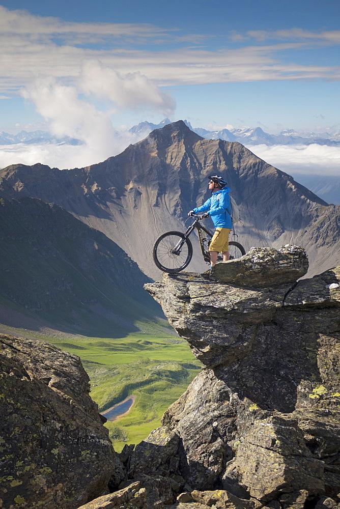 Mountain Biker Standing On Top Of Rock Near The Weisshorn In Switzerland
