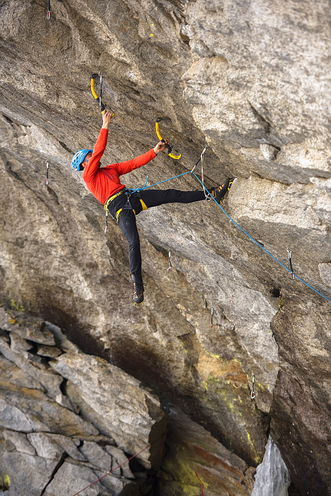 Male Ice Climber Climbing And Drytooling On Rock