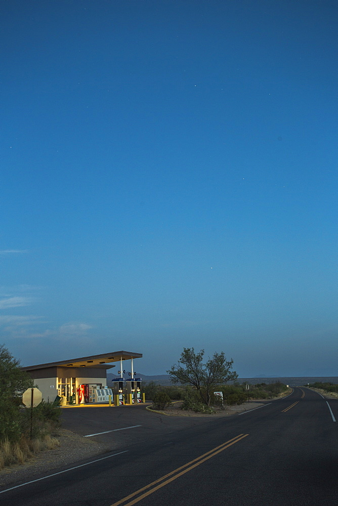 A Vintage Gas Station Glows Beside An Empty Desert Road At Dawn