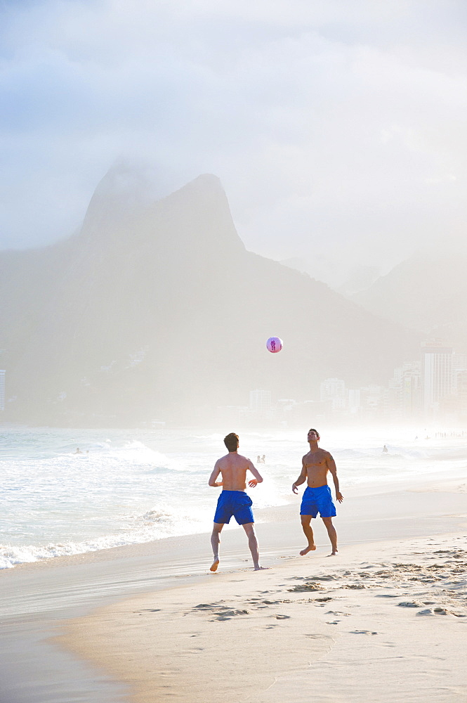 Two Men Playing Soccer In The Surf On Ipanema Beach, Rio De Janeiro, Brazil