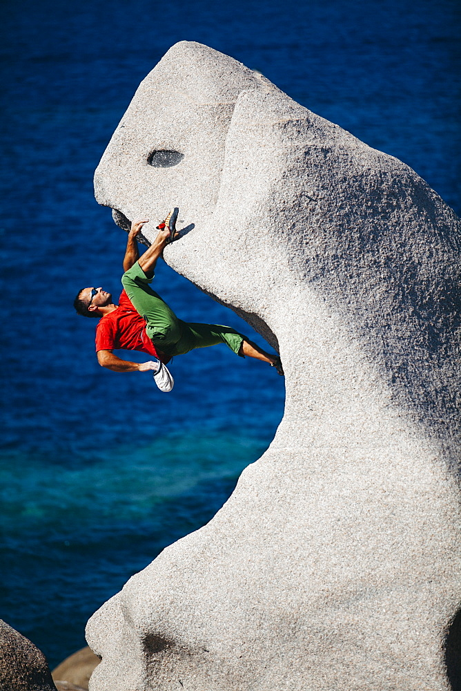 Man climbing on rock near sea, Capo Testa, Sardinia, Italy