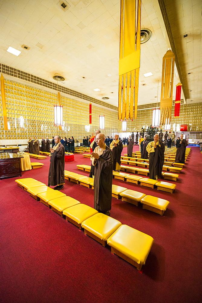 Monks praying in The Jeweled Hall of 10, 000 Buddhas, Ukiah, California, USA