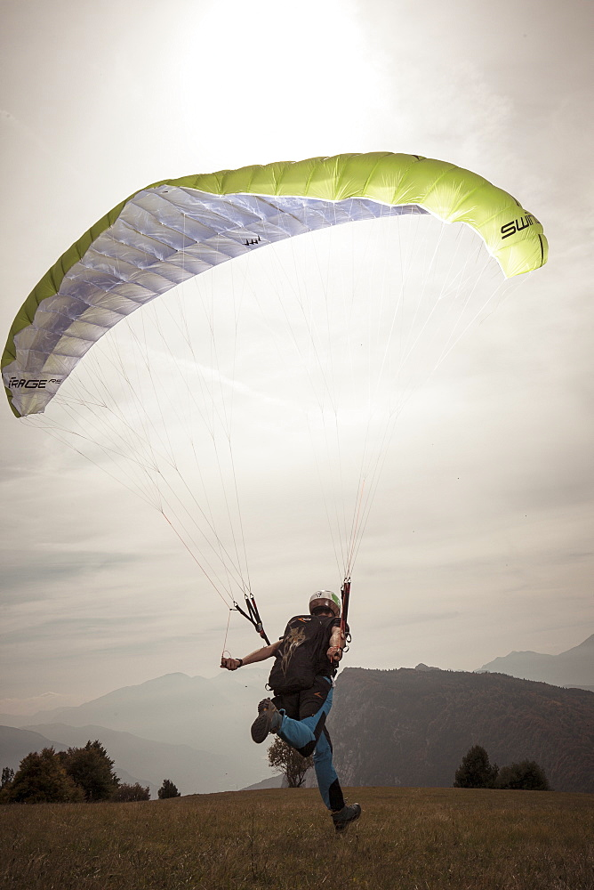 Paraglider landing softly on grass in front of hills, Brento, Venetien, Italy