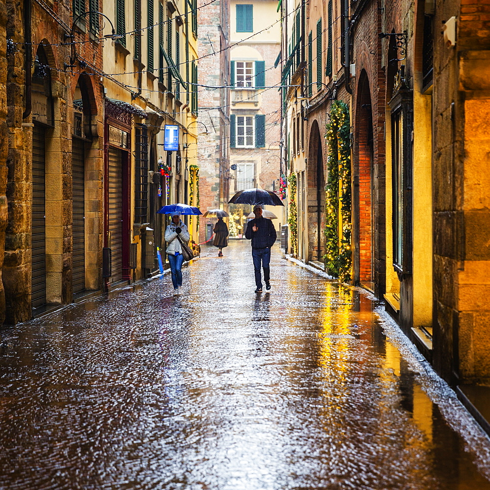 People walking the wet city streets in Lucca, a city and commune in Tuscany, Central Italy, on the Serchio, a fertile plain near the Tyrrhenian Sea. It is the capital of the Province of Lucca. It is famous for its intact Renaissance-era city walls. - 857-95487