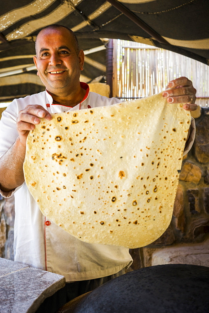 Happy Chef holding up freshly cooked, handmade shrak (markook) Bedouin bread, Wadi Rum Village, Aqaba Governorate, Jordan