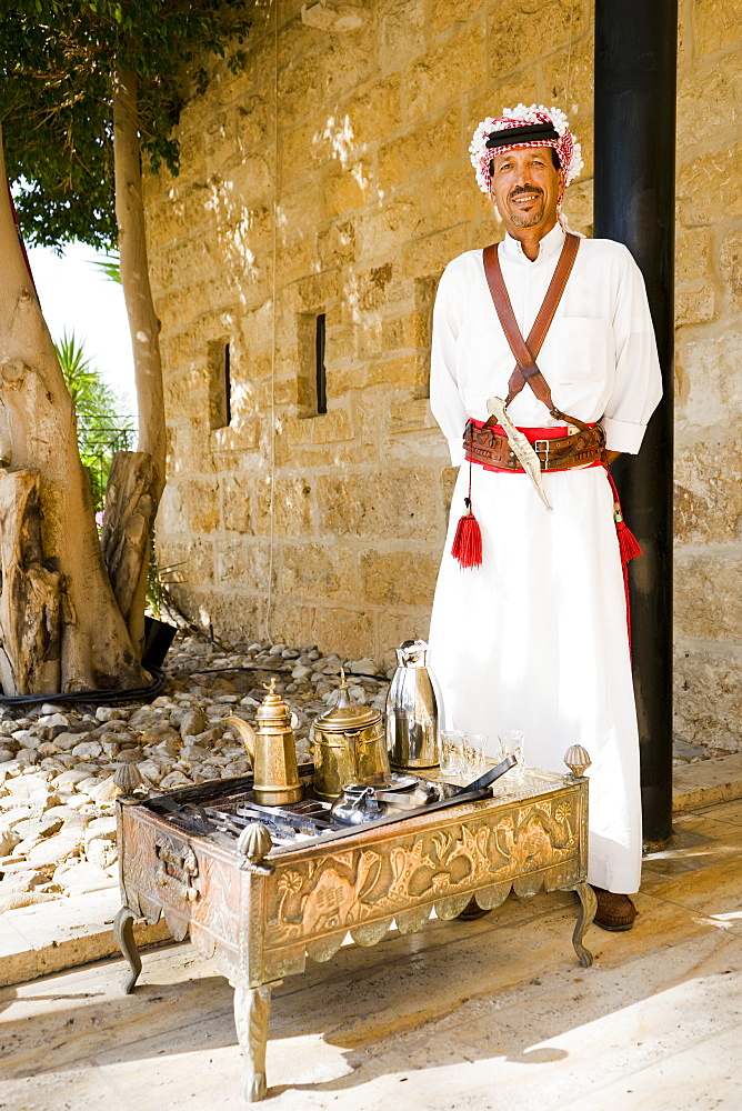 Portrait of man wearing traditional Arabic clothes standing by traditional tea set on engraved tea table, Madaba Governorate, Jordan