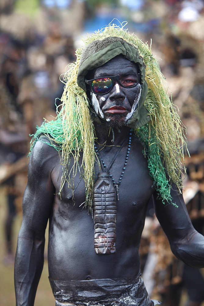 Funny man with skin painted black and green hairpiece on blurred background at Ati Atihan festival, Kalibo, Aklan, Panay Island, Philippines - 857-95631