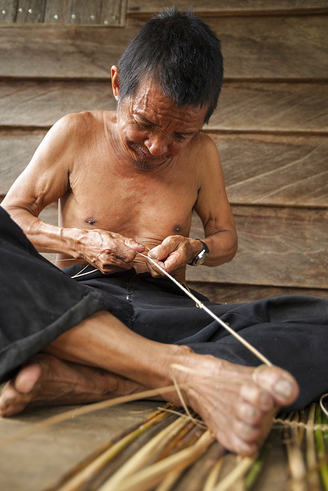 Man weaving a traditional fish basket - Borneo Indonesia