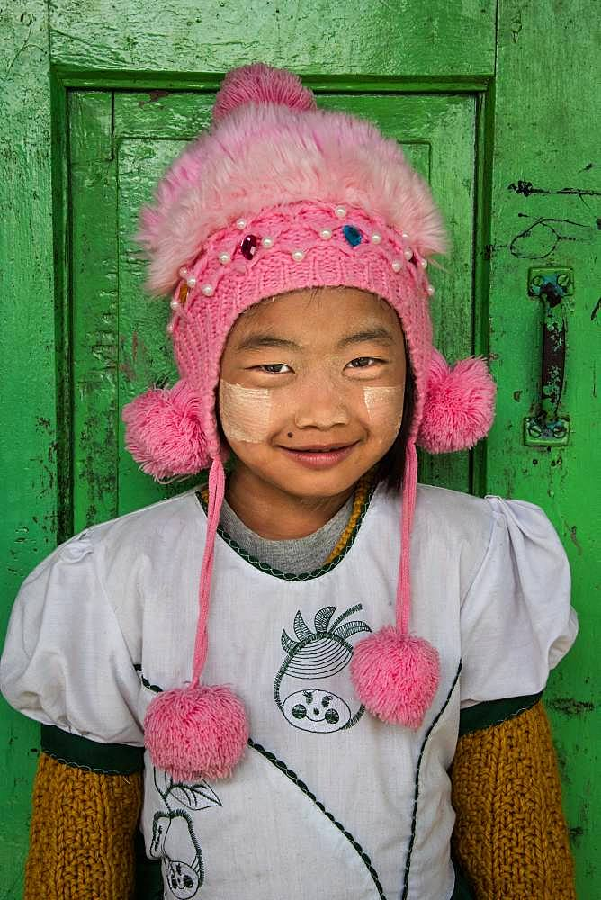 Burmese girl with her pompom cap, photographed in front of her classroom in the city of Nyuang U. On these cheeks, tanakha powder, to protect from the sun.