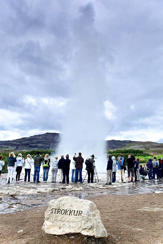 Tourists watching the gushing of a geyser: hot water coming out of the Strokkur geyser, Geysir site, Iceland.