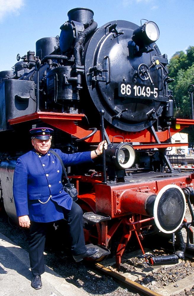 historical steam locomotive typ 86 1049-5 on rails in rail station and railway official wearing historical uniform portrait Annaberg-Buchholz Sachsen Deutschland