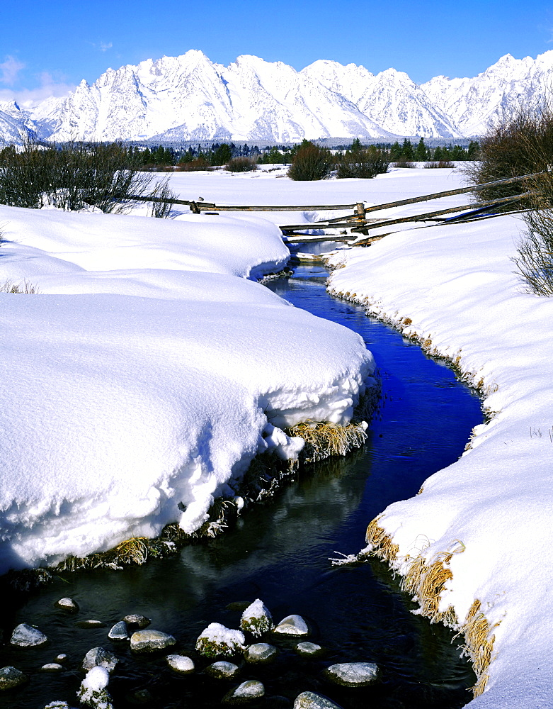 splitrail fence across a stream below the Teton Range in winter Grand Teton National Park Wyoming USA   - 869-5212