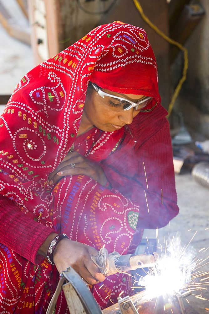 Women welding joints during the construction of solar cookers at the Barefoot College in Tilonia, Rajasthan, India. The Barefoot College is a worldwide charity, founded by Bunker Roy, its aims are, education, drinking water, electrification through solar power, skill development, health, women empowerment and the upliftment of rural people. Solar cookers save women having to walk to the froest to cut down wood for cooking, thus saving the forests, and a daily chore for woman. - 911-10062