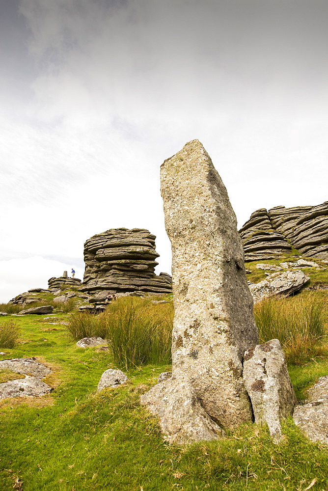 A granite Tor and standing stone on the summit of Great Links Tor, on Dartmoor, Devon, UK.