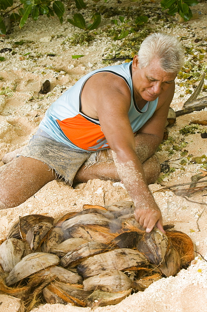 A Tuvaluan man prepares a traditional pit fire on Tepuka island off Funafuti Atoll, Tuvalu, Pacific