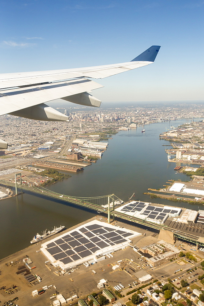 Approaching Philadelphia, over the Benjamic Franklin Bridge on the Delaware River, with harbour front warehouses covered in solar panels. USA.