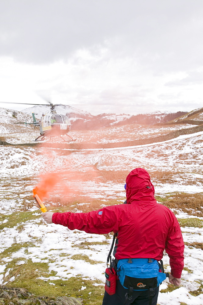 A member of Langdale Ambleside Mountain Rescue Team attracts an air ambulance with a flare to the site of an injured walker on Silver Howe above Grasmere, Lake District, Cumbria, England, United Kingdom, Europe