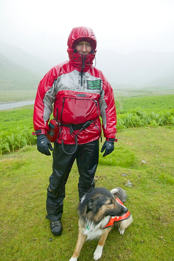 A  search dog handler as a Member of Langdale Ambleside Mountain Rescue Team on a rescue on a very wet day, Lake District, Cumbria, England, United Kingdom, Europe