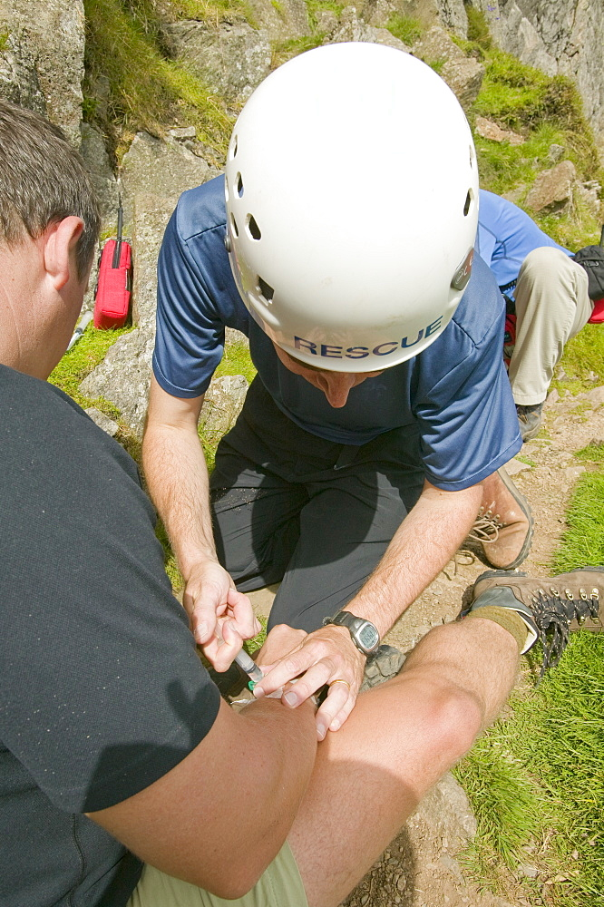 Mountain rescue team doctor injects an injured climber with morphine for pain relief after he dislocated his shoulder on Jacks Rake, Pavey Ark, Lake District, Cumbria, England, United Kingdom, Europe