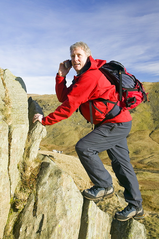 A climber on Red Screes using a mobile phone, Lake District, Cumbria, England, United Kingdom, Europe
