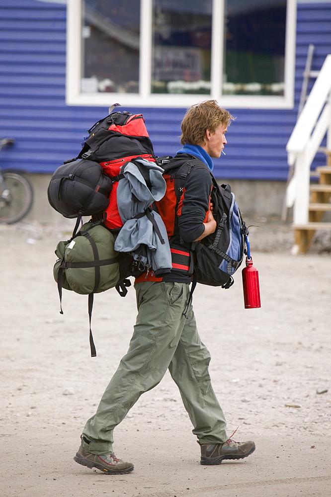 Traveller weighed down with heavy rucksacks in Ilulissat, Greenland, Polar Regions