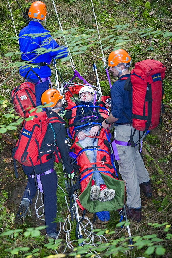 Members of the Langdale Ambleside Mountain Rescue Team treat an injured walker in the Lake District, Cumbria, England, United Kingdom, Europe
