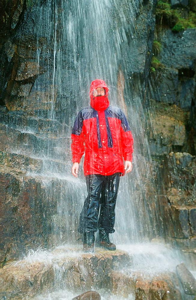 A man testing a waterproof jacket under a waterfall in Scotland, United Kingdom, Europe