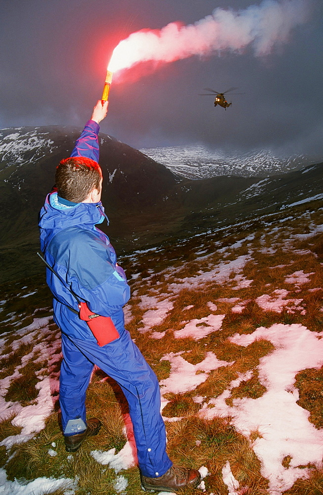 A mountain rescue member uses a flare to attract an approaching Sea King helicopter to the casualty site on Fairfield in the Lake District National Park, Cumbria, England, United Kingdom, Europe
