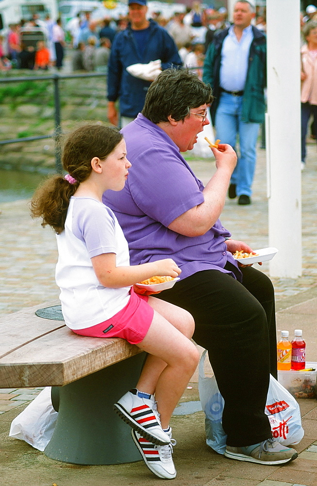 A fat women and daughter easting chips, Whitehaven, Cumbria, England, United Kingdom, Europe