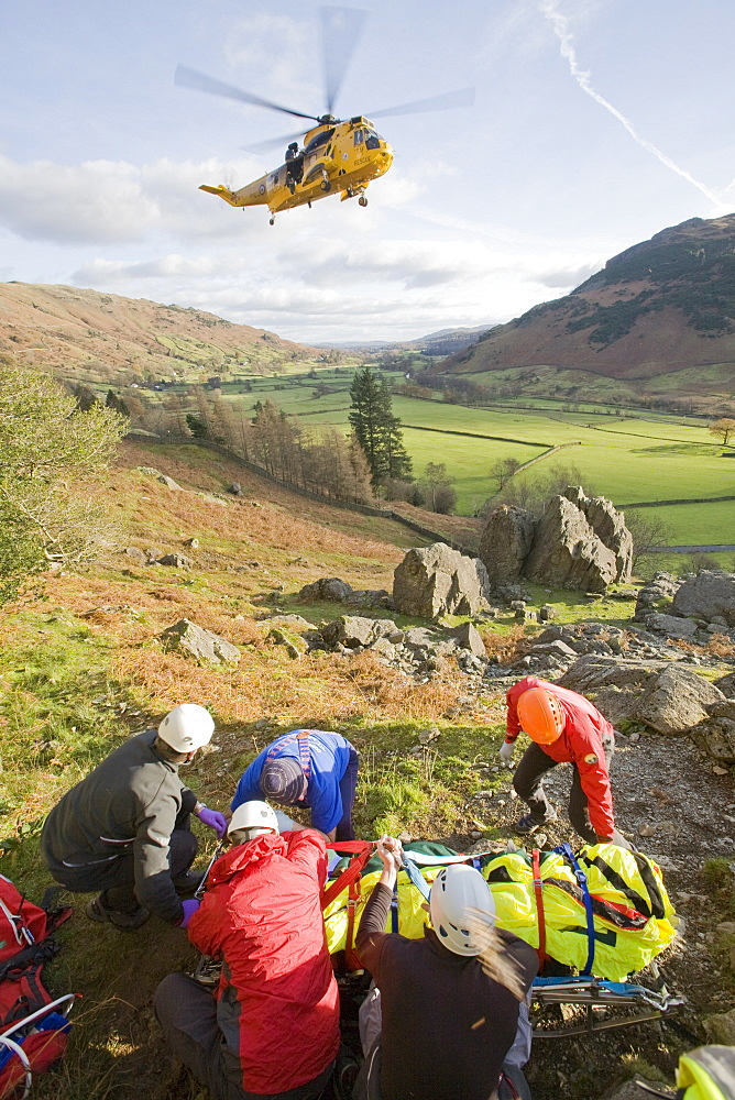 Members of Langdale Ambleside Mountain Rescue Team treat a seriously injured climber with a broken femur in the Langdale Valley, Lake District, Cumbria, England, United Kingdom, Europe