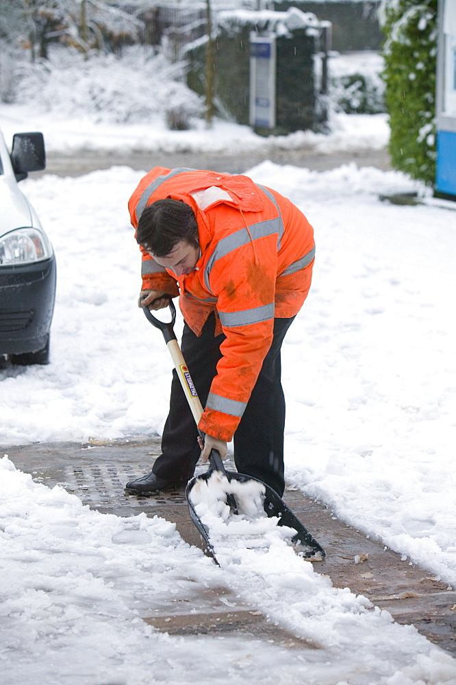 A man shovelling snow at Windermere Train Station, Cumbria, England, United Kingdom, Europe