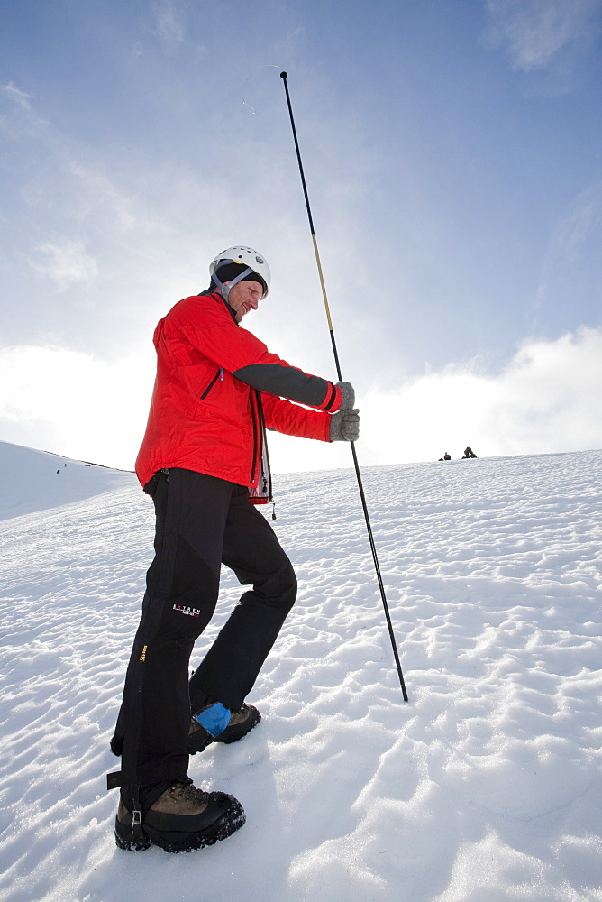 A member of the Scottish Avalanche Information Service demonstrates how to use an avalanche probe on Cairngorm in the Cairngorm National Park in Scotland, United Kingdom, Europe
