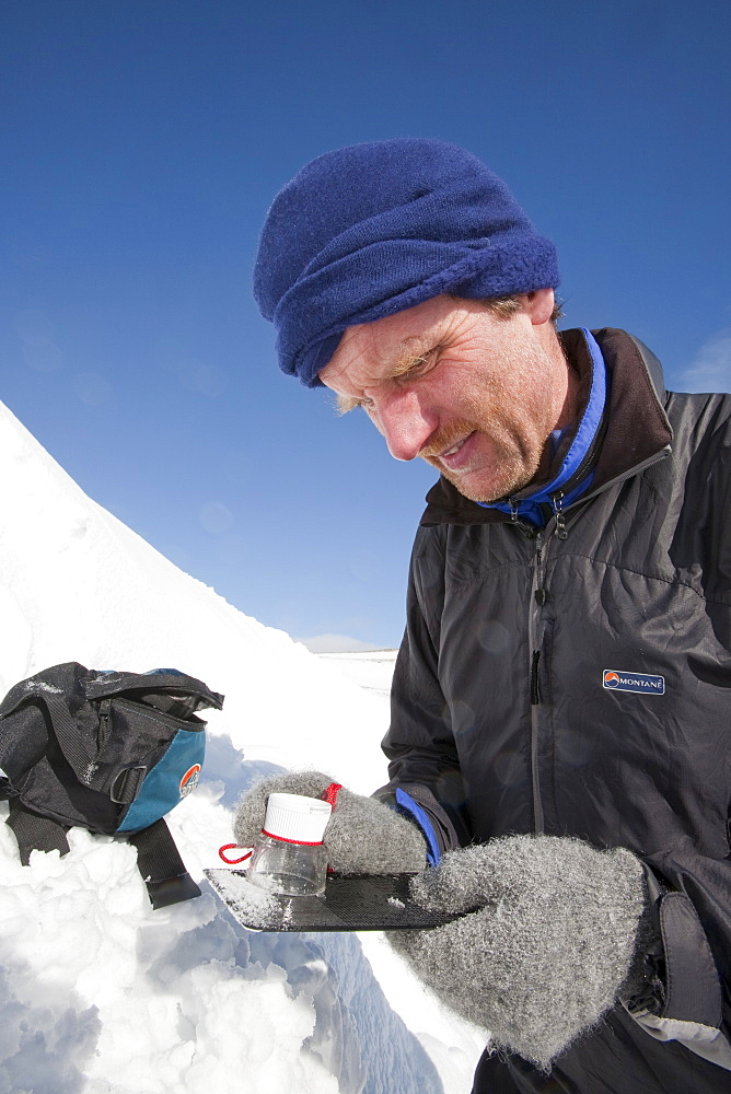 A member of the Scottish Avalanche Information Service looks at snow crystals to help assess avalanche risk on  Cairngorm in the Cairngorm National Park in Scotland, United Kingdom, Europe