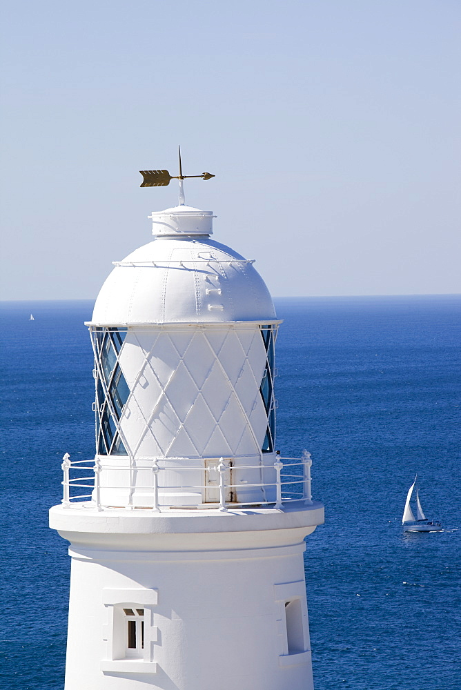 A sailing boat sails past Pendeen Watch lighthouse near St. Just in Cornwall, England, United Kingdom, Europe