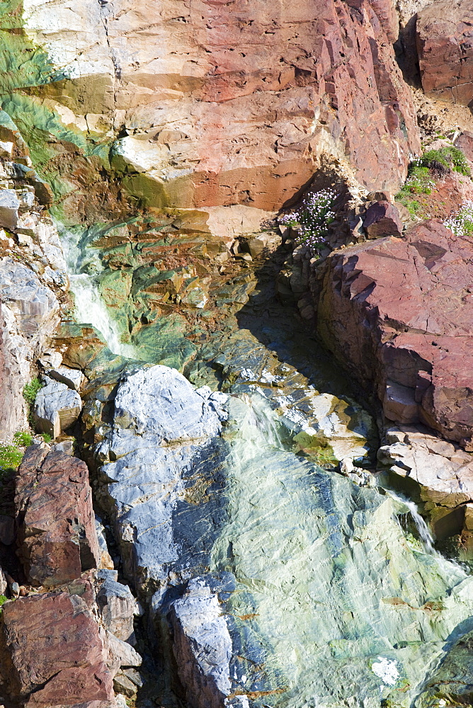 Sea cliffs stained green from copper deposits leaching from the old Geevor Tin Mine near St. Just in Cornwall, England, United Kingdom, Europe