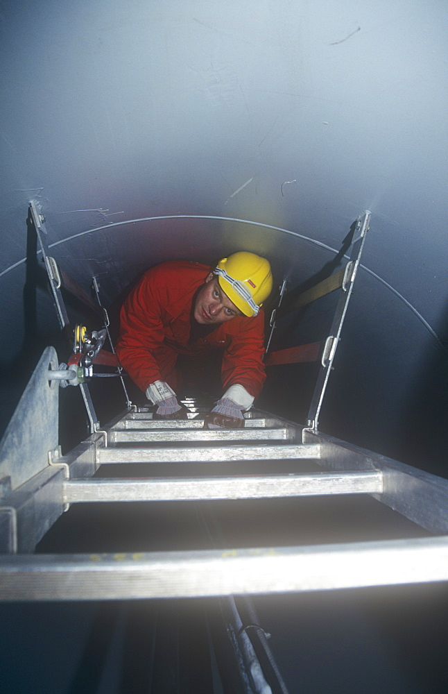 An engineer climbs up the inside of a wind turbine above Ulverston, Cumbria, England, United Kingdom, Europe