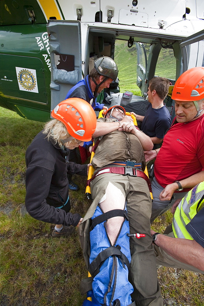 Paramedics from the Great North Air Ambulance and members of Langdale/Ambleside Mountain Rescue Team treat an injured man who fell into Wrynose Beck, before transferring him to hospital via helicopter. Lake District, Cumbria, England, United Kingdom, Euro