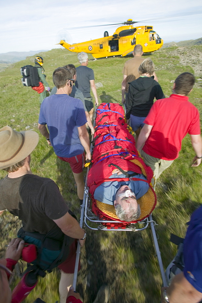 Memers of Langdale Ambleside mountain rescue team evacuate an injured walker on Bow Fell in the Lake District, Cumbria, England, United Kingdom, Europe