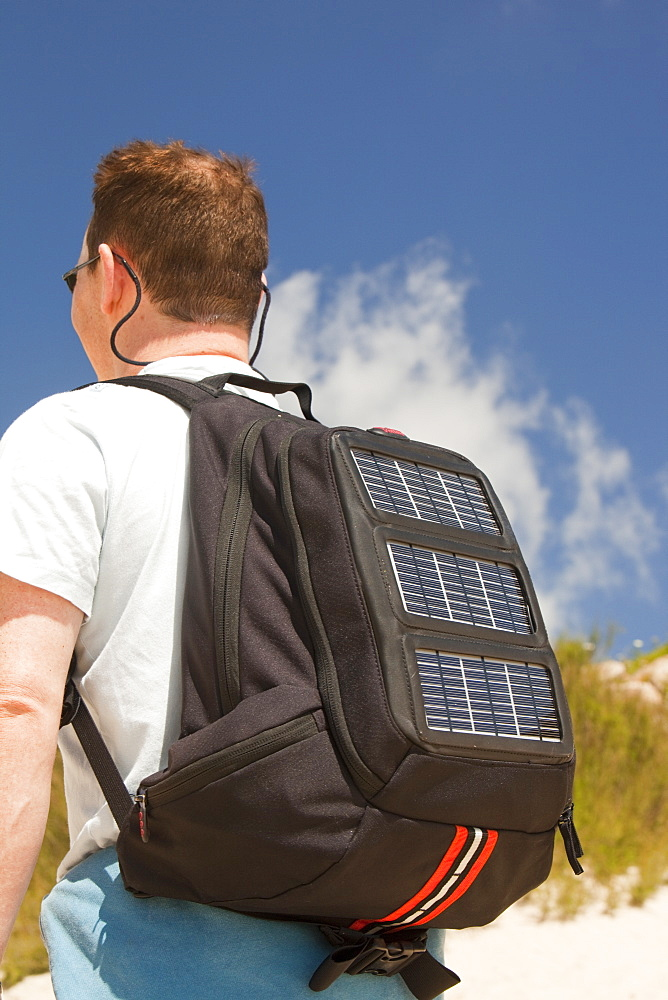 A man carrying a solar backpack, the solar panels can be used for recharging mobile phones and other electrical devices - 911-7057