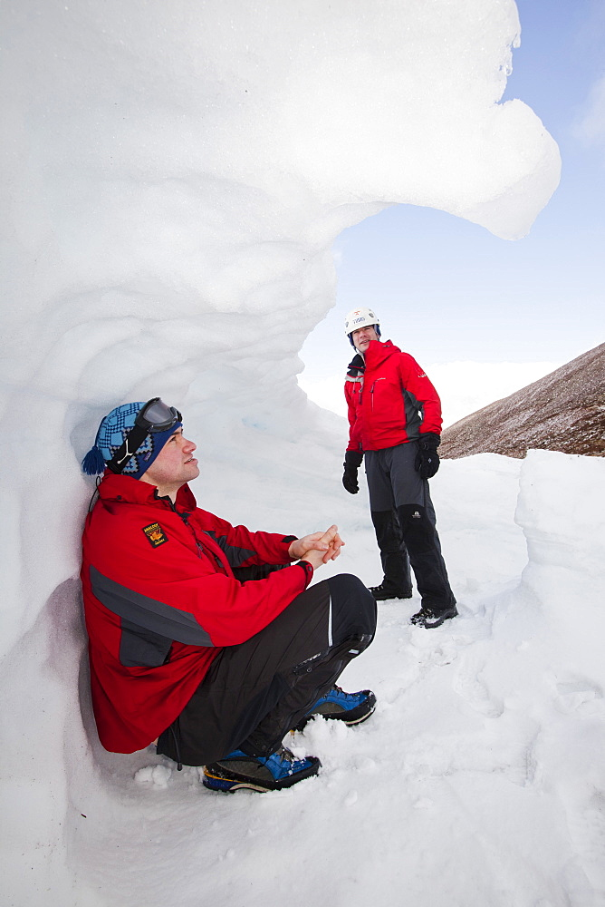 Mountaineers sheltering in an old snow hole in snow banked against an esker in Coire an Sneachda in the Cairngorms, Scotland, United Kingdom, Europe