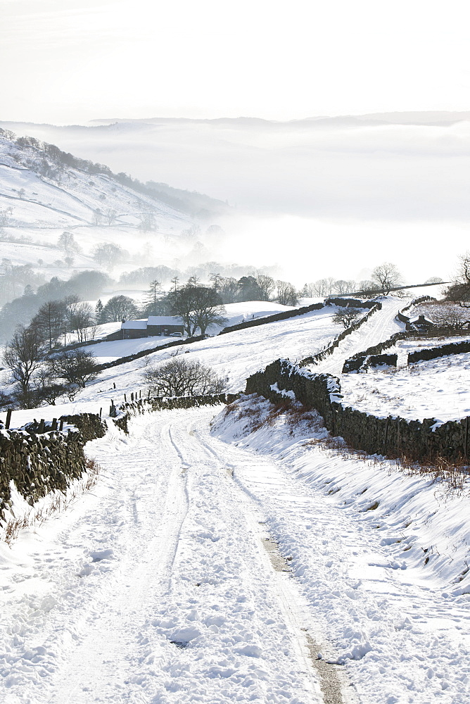 Kirkstone Pass snowed up in winter looking down towards Ambleside shrouded in valley mist, Lake District, Cumbria, England, United Kingdom, Europe
