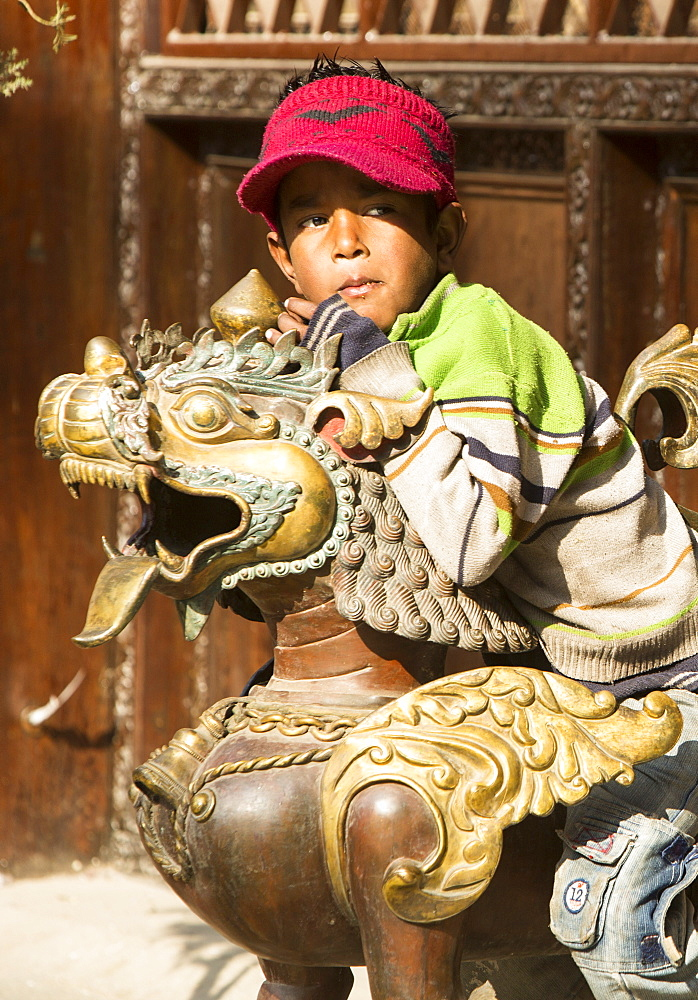 A young boy sitting on a copper sculpture at a religious site in Kathmandu, Nepal, Asia