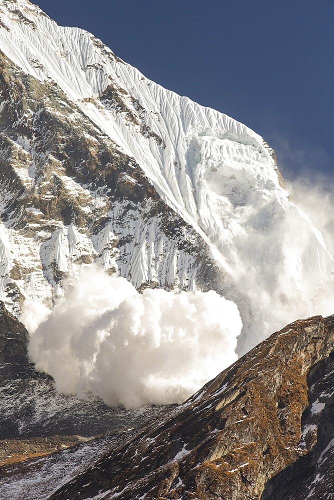 An avalanche on Machapuchare (Fishtail Peak) in the Annapurna Himalaya, Nepal, Asia