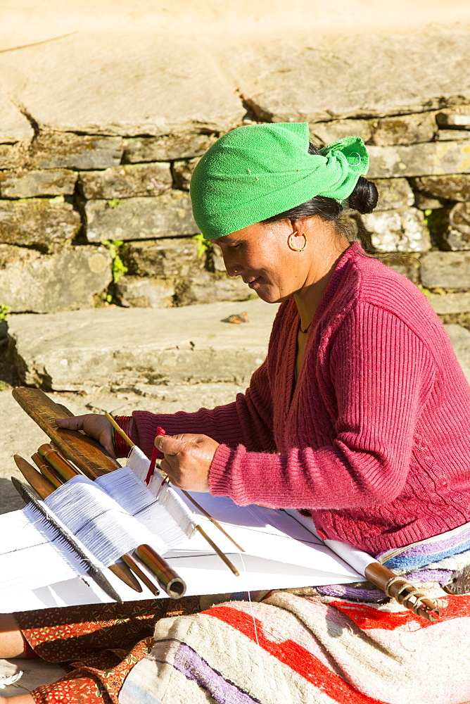 A Nepalese woman in traditional clothing weaving cloth on a hand loom in the Himalayan foothills, Nepal, Asia - 911-9321