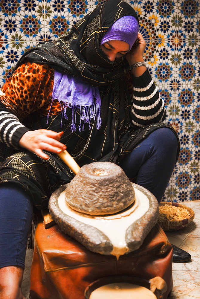 Argon / Argain Oil, considered to be one of the finest natural anti-ageing treatments for skin, traditional grinding of seeds, milling, muslim women. Taroudant, Souks, Agadir. Morocco