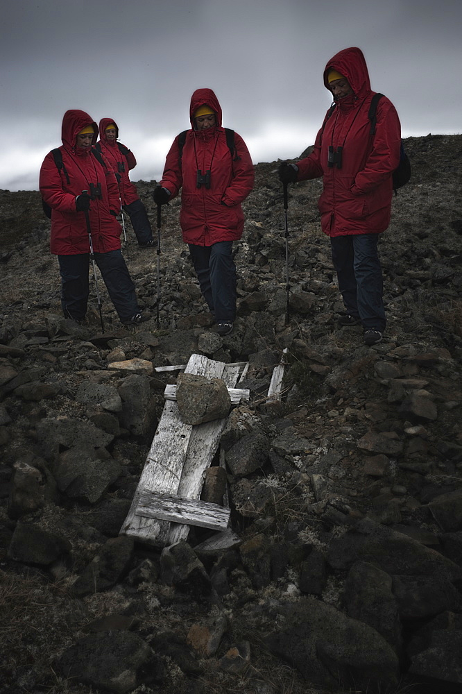 Whalebone Alley, female tourist standing around still intact extremly old inuit elder grave, skeleton still present. Itygran Island (Bering Sea) Russia, Asia.  MORE INFO: Whale Bone Alley was discovered by Soviet archaeologists in 1976, but has remained untouched since and little is known of this place. There is a long double line of bowhead whale bones -- jaws and ribs -- running parallel along the shore for hundreds of yards. Many of the bones, especially the enormous jaw bones, are still standing, propped up by lichen-covered rocks. The location is thought to have been used in about 1300 as a ceremonial site, for a men's secret society or feasting site.