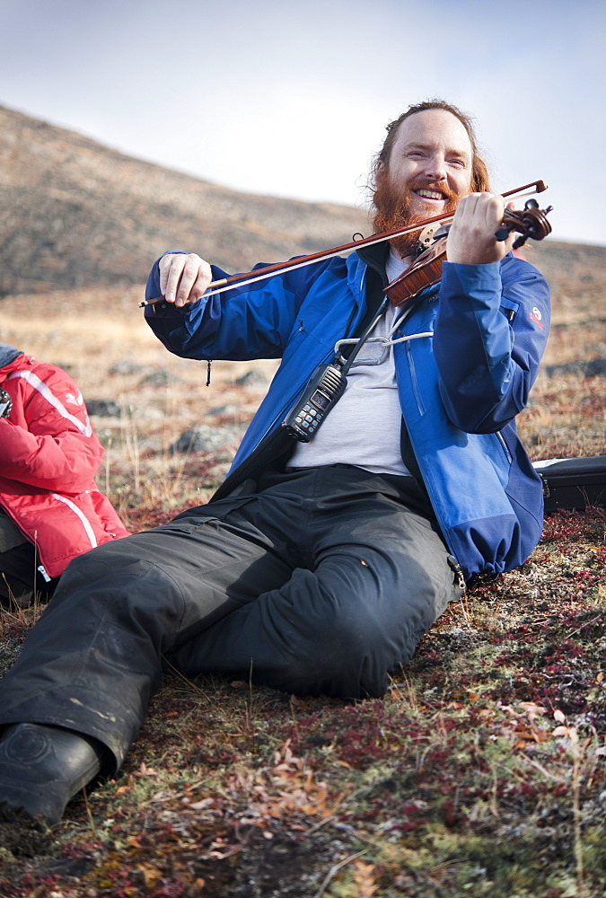 Musician Daniel Payne playing fiddle on mountain side. Pangnirtung, Cape Dyer, Baffin Island, Canada, North America