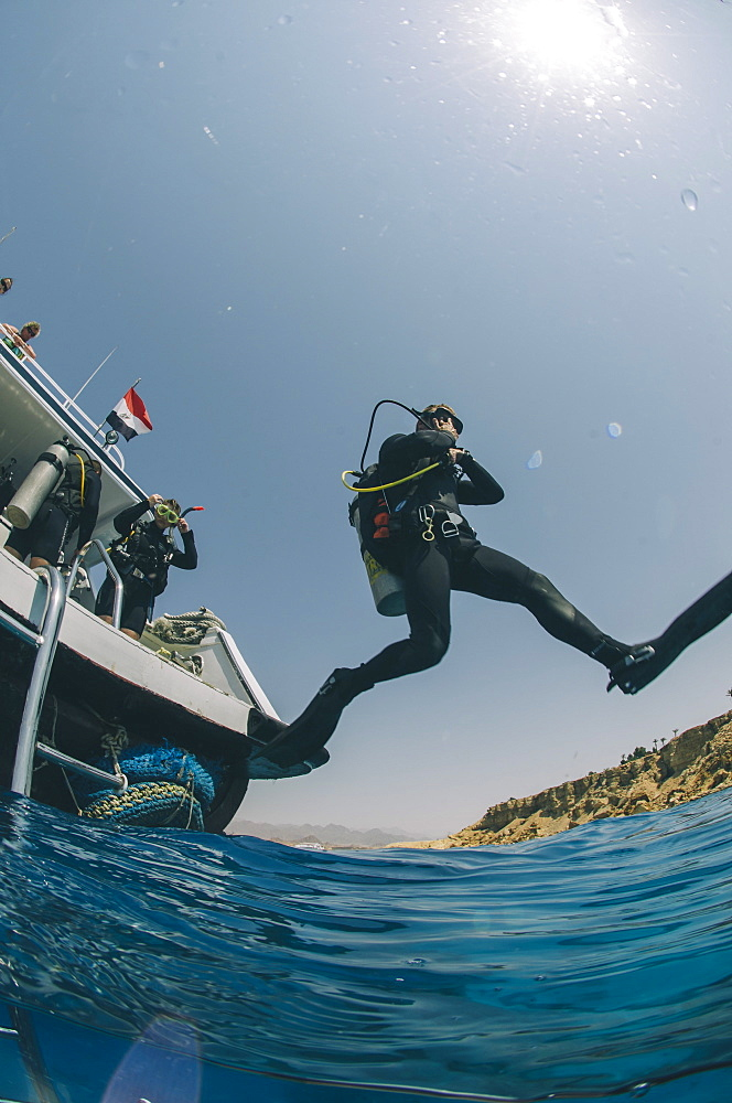 Scuba diver making giant stride entry into the water, Red Sea, Egypt, North Africa, Africa - 974-421